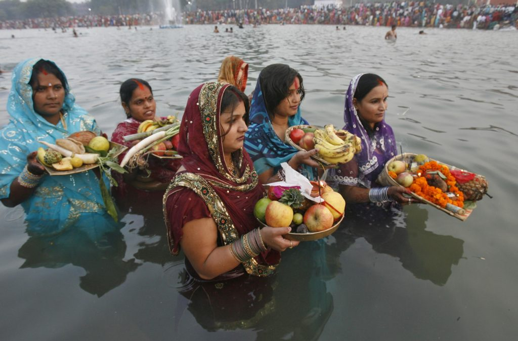 "Hindu devotees offer prayers to the Sun god during the Hindu religious festival ""Chhat Puja"" in the northern Indian city of Chandigarh November 1, 2011. Hindu devotees worship the Sun god and fast all day for the betterment of their family and society during the festival. REUTERS/Ajay Verma (INDIA - Tags: RELIGION SOCIETY)"
